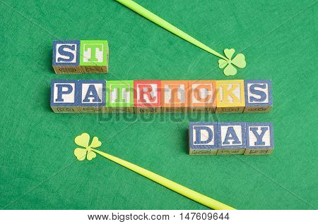 PreviewSave to a St Patrick's day spelled with colorful alphabet blocks displayed with two four leaf clovers on a green background