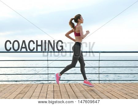 Word COACHING on background. Business trainer concept. Young woman running on pier