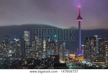 Cloud's edge cuts through hot humid night time air in Toronto, Canada.  Long exposure of urban illuminated skyline as glowing rain cloud quickly moves in to the downtown core.