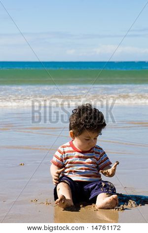 Baby seated on beach and playing with sand