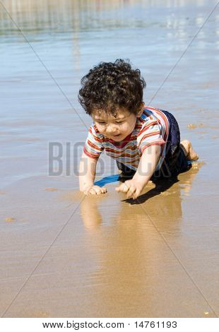 Baby crawling on beach and playing with sand