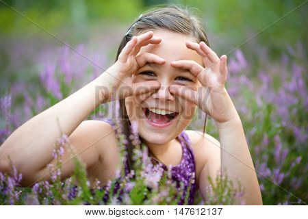 Girl in heather flowers showing glasses gesture, outdoor shoot
