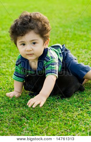 cute baby boy playing with little black chow puppy