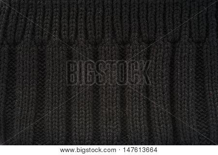 Rib knit of black melange wool yarn as background.