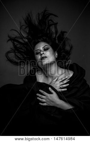 lying, sad woman with large black cloth on the body, long-haired brunette