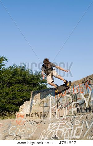 teen boy skateboarder playing on concrete ramp