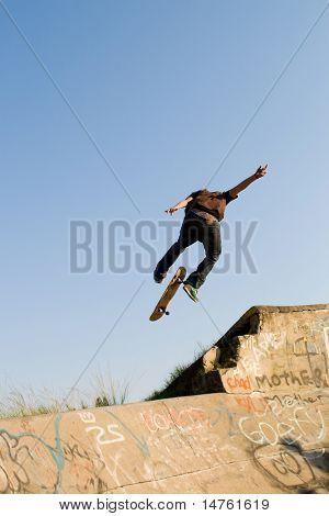 teen boy skateboarder playing on concrete ramp