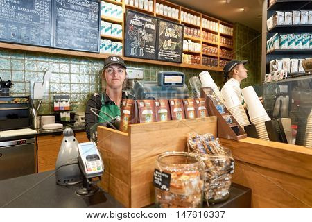 MOSCOW, RUSSIA- AUGUST 24, 2016: indoor portrait of a worker at Starbucks Cafe. Starbucks Corporation is an American coffee company and coffeehouse chain.