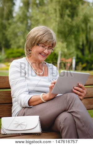 Attractive mature woman sitting on a bench holding and using a digital tablet in the park at summer day