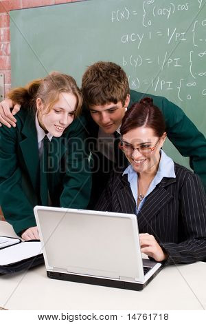 attractive school teacher teaching computer lesson to her students