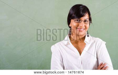 young beautiful school teacher standing in front of blackboard