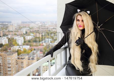 Beautiful blond woman in costume of cat is sitting on balcony with black umbrella