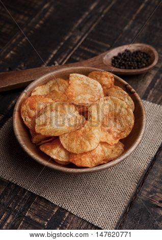 Bowl with potato crisps chips with pepper on wood. Potatoes and pepper