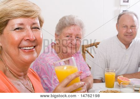 happy seniors friends having breakfast together
