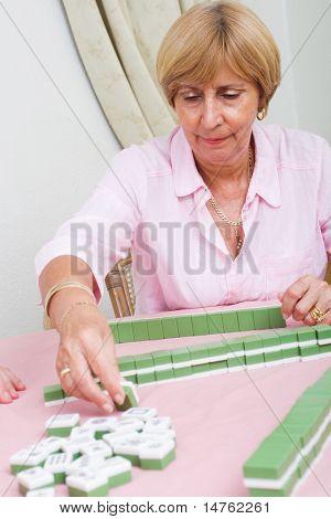 senior woman playing mah jong game
