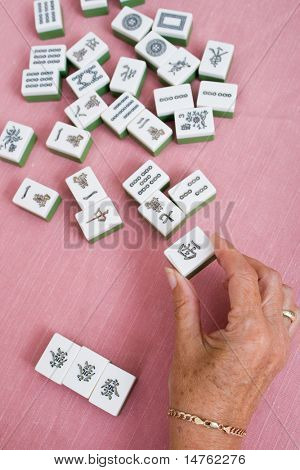senior woman hand holding a piece of mahjong tile