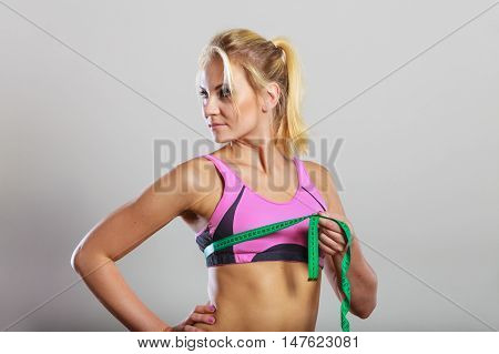 Weight loss slim body healthy lifestyle concept. Fit fitness woman in sport bra measuring her chest breasts with green measure tape