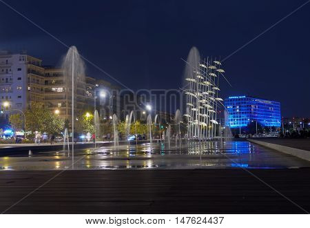 Thessaloniki, Greece - September 12 2016: Seafront night umbrellas and fountains. Makedonia Palace hotel is visible in the background.