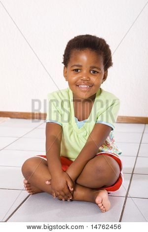 african american little girl sitting on floor a home