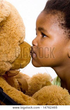 cute african american little girl kissing teddy bear