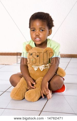 african little girl sitting on floor and hugging her teddy bear