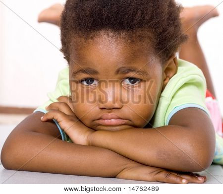 african american little girl lying on floor