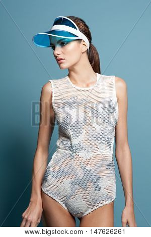 Fashion Female In Sun Visor And Swimsuit On Blue Background
