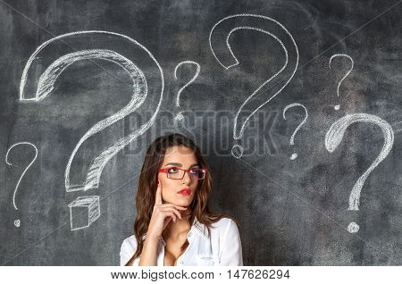 Young Female Businesswoman In Glasses Arrounded Question Marks