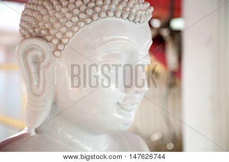 Beautiful white stone Buddha statue head. Buddhism sculpture calm peaceful face