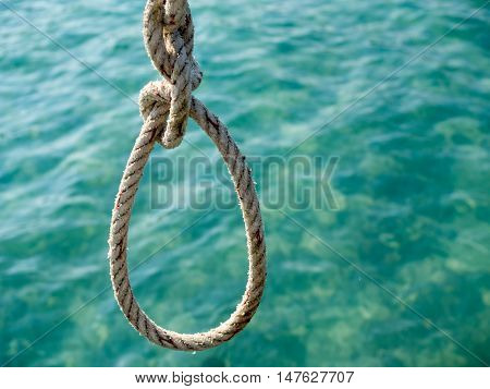 White rope hanging over crystal green sea. Safe life equipment for travel in sea. Tropical summer vacation concept.