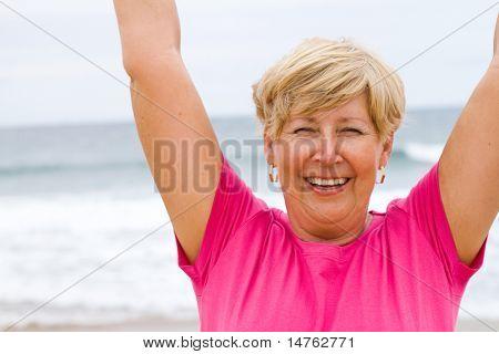 happy elderly woman doing exercise on beach