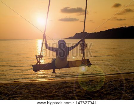 Silhouette of woman on a rope swing that hang over beach at sunset. Concept of relax enjoy joyful in summer.