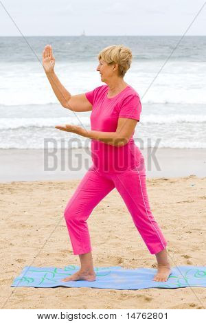senior woman doing Tai Chi exercise on beach