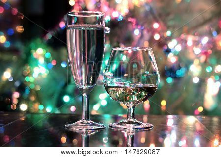 glasses of brandy and wine on festive background