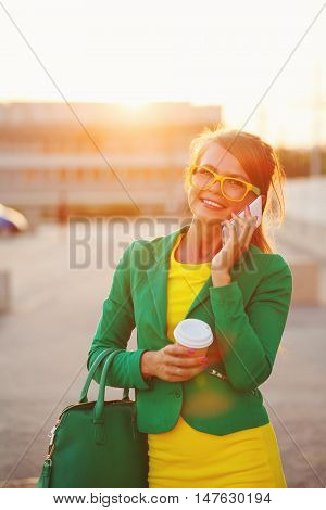 Young attractive woman talking on cell phone. Businesswoman holding a cup of coffee and fashionable bag. A successful and positive. Soft focus.