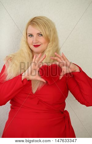 Young woman in red dress with low neckline is holding heart jewel case
