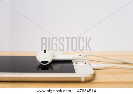 CHIANGRAI THAILAND -SEPTEMBER 15 2016: Side view of new Apple Lightning EarPods mockup on top of new Apple iPhone 7 mockup and reflection on screen on wooden table.