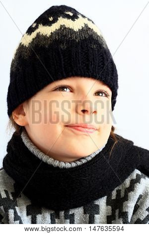 Little girl in knitted hat and scarf on a white background.