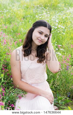 Pretty girl sits on a richly meadow