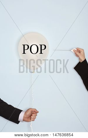 Cropped hands holding needle and popping balloon against light blue background