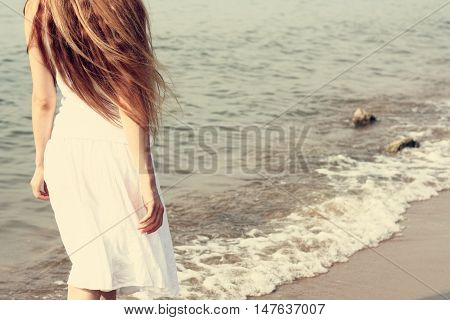 Young girl in a white dress leaves against the sea on a summer day.