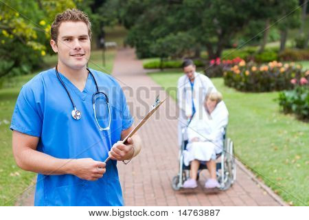 friendly young male doctor portrait outdoors, background is his colleague pushing recovery, patient in wheelchair