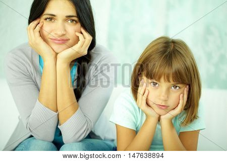 Portrait of mother and daughter looking at camera with hands on cheeks