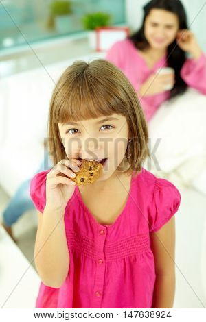 Portrait of a little girl looking at camera and eating cookie