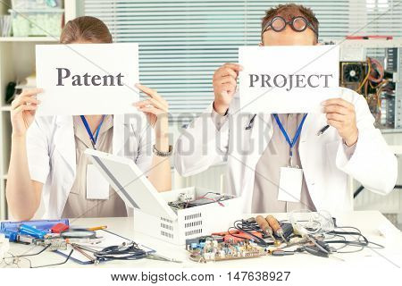 Scientists sitting at the table and holding placard with the words patent and project in front of their faces
