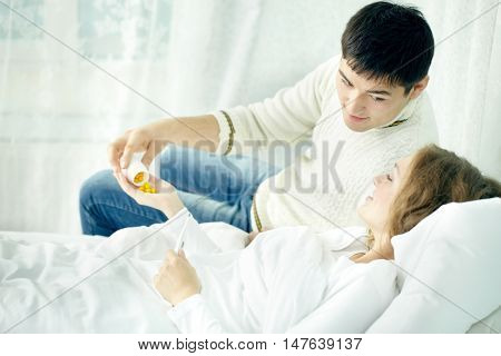 Young man giving vitamins to his wife lying on bed