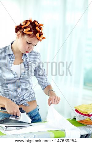 Woman with curlers is bored to iron linen
