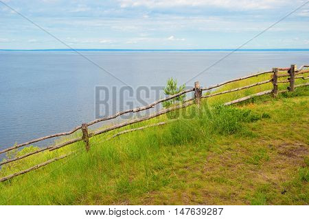 Landscape with a river and a wooden fence