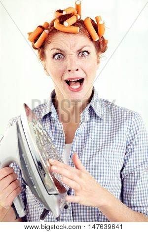 Portrait of woman in curlers shouting with pain on being burned from iron