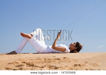 young woman relaxing and lying on beach reading sms from a cellphone